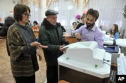 Members of an election commission help a man, center, to cast his ballot in the presidential election in Yekaterinburg, Russia, Sunday, March 18, 2018.