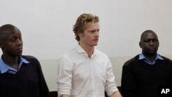 Jack Alexander Loup Marrian, ressortissant britannique accusé du trafic de cocaïne, comparaît entre deux policiers lors d'une audience au tribunal de Kibera à Nairobi, Kenya, 4 août 2016.
