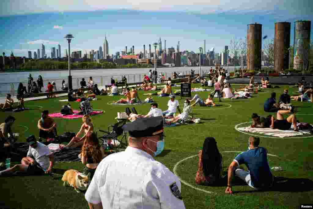 نیویارک میں کئی لوگ دن بھر پڑنے والی گرمی کے بعد شام کو پارکس کا رُخ کرتے ہیں۔ ایسے میں سماجی فاصلوں پر عمل درآمد کے لیے پارکس میں بھی سفید دائرے لگا کر لوگوں کے درمیان فاصلہ رکھا گیا ہے۔