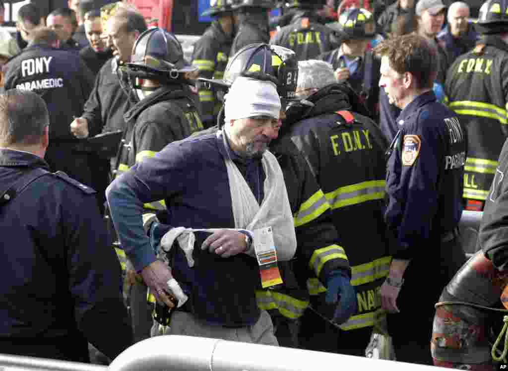 An injured passenger of the Seastreak Wall Street ferry is aided by firefighters, New York, January 9, 2013.