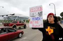 FILE - Native American Steve Morales, of Dallas, holds up a sign as he joins others in protest outside of an NFL football game between the Washington Redskins and Dallas Cowboys in Arlington, Texas, Oct. 13, 2013.