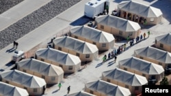 FILE - Immigrant children housed in a tent encampment under the zero tolerance policy by the Trump administration are shown walking in single file at the facility near the Mexican border in Tornillo, Texas, June 19, 2018.