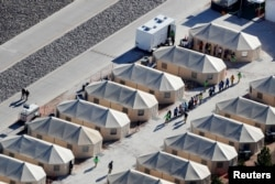 "Immigrant children currently housed in a tent encampment under the new ""zero tolerance"" policy by the Trump administration are shown walking in single file at the facility near the Mexican border in Tornillo, Texas, June 19, 2018."