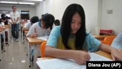 Elementary students are seen studying in a small cram school in hopes of success on their high school entrance exams, Tuesday, July 6, 2010, in Taipei, Taiwan. Taiwanese students spent months preparing for tests that will determine whether they to an elit