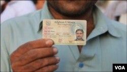 کراچی کی افغان بستی کے رہائشی گل احمد اپنا رجسٹریشن کارڈ دکھارہے ہیں۔