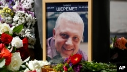 Foto Pavel Sheremet yang dikelilingi bunga dan lilin di tempat kematiannya (20/7). Kiev, Ukraina. (foto: AP Photo/Sergei Chusavkov)