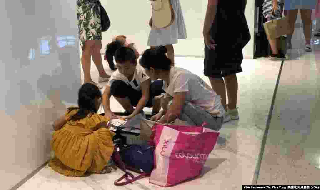 尖沙咀海港城商場內隨處可見中國遊客蹲在地上收拾行李箱 (美國之音湯惠芸)