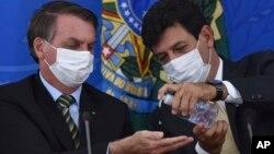 Le ministre brésilien de la santé Luiz Henrique Mandetta appliquant du gel désinfectant sur les mains du président Jair Bolsonaro lors d'une conférence de presse sur le Covid-19, au palais présidentiel Planalto, Brasilia, 18 mars 2019. (Photo AP/André Borges)