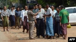 A prison official checks documents before a group of regular prisoners are freed from Insein prison in Yangon, April 8, 2016.