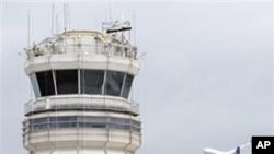 图为一架客机3月24日飞过首都华盛顿里根机场的联邦航空管理局控制塔