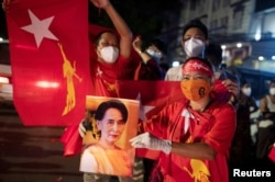 A supporter of National League for Democracy holds a picture of Myanmar State Counselor Aung San Suu Kyi as she waits for results outside the party headquarters after the general election in Yangon, Myanmar, November 8, 2020. REUTERS/Shwe Paw Mya Tin
