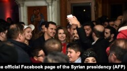 Syrian President Bashar al-Assad, center left, and his wife, Asma al-Assad, center right, pose for a picture with a Syrian man at a Christmas choral presentation at the Lady of Damascus Catholic Church, in Damascus, Dec. 18, 2015.