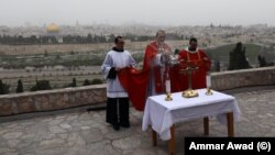 Uskup Agung Perbattista Pizzaballa dari Latin Patriarchate Yerusalem dan pemimpin Katolik Roma lainnya menggelar misa di Gunung Zaitun yang menghadap tembok-tembok Kota Tua Yerusalem. Tidak ada prosesi Minggu Palem seperti sebelumnya karena wabah virus corona, 5 April 2020.
