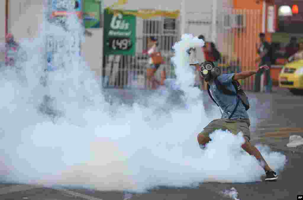 A demonstrator get ready to throw a tear gas grenade back to the police, outside the central train station, during protest against the increase on bus fares in Rio de Janeiro, Feb. 6, 2014.