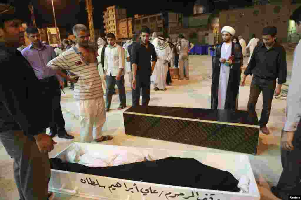 Mourners stand beside coffins of four members of a family killed in Basra bomb attacks, during a funeral in Najaf, Iraq, May 20, 2013.