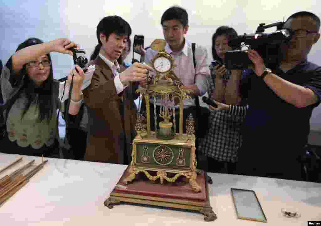 Guo Fuxiang (2nd L), a researcher of the Palace Museum, introduces the damaged Qing Dynasty clock to journalists during a media briefing at the Forbidden City in Beijing, China. A man broke a window with his bare hands while touring the museum, knocking the clock onto the ground and causing the damage.