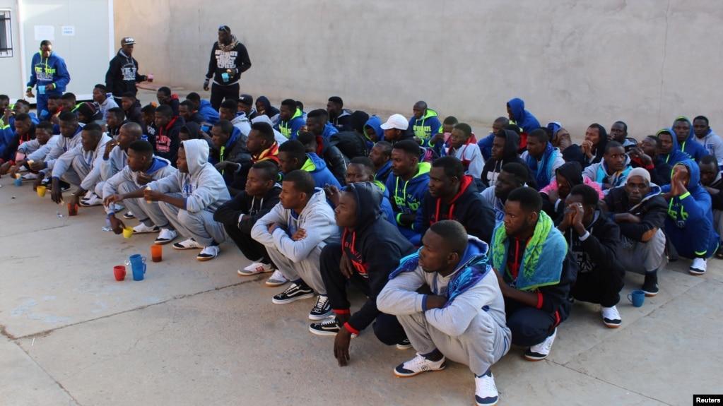 FILE - Migrants wait before being deported by Libyan authorities, in Misrata, Libya, Feb. 19, 2018.