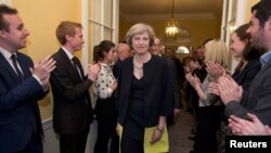 Para staf kantor Perdana Menteri Inggris menyambut PM baru Inggris Theresa May di Jalan Downing 10, usai pelantikannya hari Rabu (13/7).