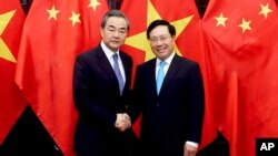 Chinese Foreign Minister Wang Yi, left and Vietnamese Foreign Minister Pham Binh Minh shake hands in Hanoi, Vietnam, April 1, 2018.