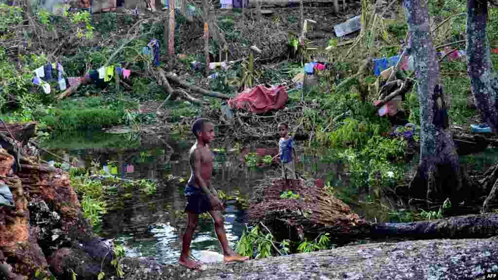 Des enfants jouent au milieu des debris d'arbres tombés à l'extérieur de la capitale de Vanuatu, Port-Vila, après le cyclone Pam qui a frappé la nation insulaire, le 17 mars 2015.