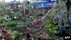 Children play in water amongst the debris of fallen trees just outside Vanuatu's capital, Port Vila, after Cyclone Pam ripped through the island nation, March 17, 2015.