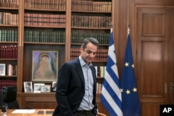 FILE - Greece's Prime Minister Kyriakos Mitsotakis waits for a meeting with Klaus Regling, Managing Director of EMS (European Stability Mechanism), in his office, in Athens, March 7, 2020.