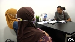 """""""Noradhiah"""" and """"Shahirah"""" listen and watch the Muslim Consumer Association Malaysia hold a phone call to start a negotiation with a loan shark's henchman. (Dave Grunebaum/VOA)"""
