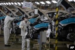 工人们佩戴口罩在位于湖北省武汉市的汽车装配线上工作。(2020年4月8日)