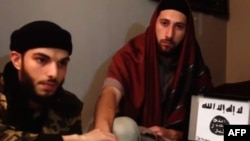 An image grab taken from a video released July 27, 2016, by Amaq News Agency, an online service affiliated with the Islamic State (IS) group, purportedly shows the two men who stormed into a church in the northern French town of Saint-Etienne-du-Rouvray and cut the throat of a 86-year-old priest at the altar, identifying themselves as Abu Jaleel al-Hanafi (L) and Ibn Omar (R) sitting next to the logo of the IS group while pledging allegiance to IS leader Abu Bakr al-Baghdadi.