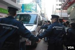 大批警員築起人鏈護送高達斌乘搭警車離開
