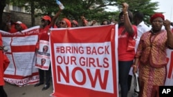 """FILE - Scores of protesters chant """"Bring Back Our Girls,"""" about Nigerian students kidnapped by Boko Haram in April 2014."""