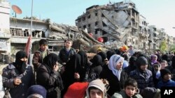 FILE - Hundreds of Syrians mingle amid rubble before going out of town to buy food and other essential materials as they wait in line at a military checkpoint in the town of Beit Sahm, south of the capital, Damascus, Syria, Jan. 14, 2015.