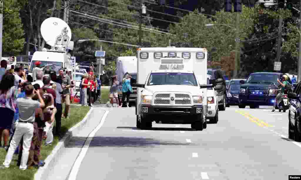 An ambulance carrying the American missionary Nancy Writebol, who was infected with Ebola in West Africa, drives past crowds of people, at Emory University Hospital, in Atlanta, Georgia Aug. 5, 2014.