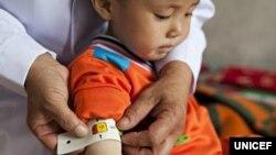 지난 2012년 6월 유니세프 직원이 북한 함경남도 함흥의 한 애육원(고아원)에서 어린이의 팔둘레를 재고있다.