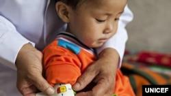 지난 2012년 6월 유니세프 직원이 북한 함경남도 함흥의 한 애육원(고아원)에서 남자 어린이의 팔둘레를 측정하고 있다. 당시 애육원에서 지내는 고아 300명 중 10%가 영양실조 상태인 것으로 파악됐다.