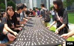 示威者在香港特區政府總部外的草地展開一幅巨型黑布,上面貼有10萬個反對國民教育的市民簽名