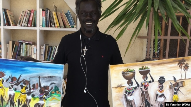 Santo Makoi poses in front of two of his recent paintings of village life in South Sudan. He says that he likes to show people what life is like back home.