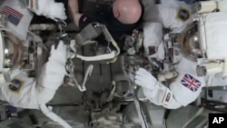 This photo taken from video provided by NASA shows astronaut Scott Kelly, center, help gather equipment for U.S. astronaut Tim Kopra, left, and British astronaut Tim Peake, as they prepare for a space walk at the International Space Station on Friday, Jan. 15, 2016.