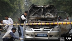Индийские оперативники обследуют взорванный автомобиль военного атташе посольства Израиля. Нью-Дели, Индия. 13 февраля 2012 г.