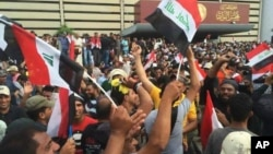 Supporters of Shiite cleric Muqtada al-Sadr raise the Iraqi flag outside parliament in Baghdad's Green Zone, April 30, 2016.
