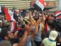 Supporters of Shi'ite cleric Muqtada al-Sadr raise the Iraqi flag outside parliament in Baghdad's Green Zone, April 30, 2016.