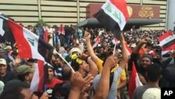 伊拉克什叶派教士穆克塔达.阿萨德的支持者在巴格达绿区内的伊拉克议会外挥舞伊拉克旗帜 (2016年4月30日)