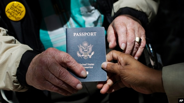 FILEe - Outside a State Department office, a World War II veteran holds his U.S. passport, June 2, 2014.