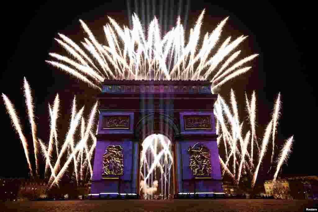 កាំជ្រួចបានបំភ្លឺផ្ទៃមេឃនៅក្លោងទ្វារ Arc de Triomphe អំឡុងការអបអរស្វាគមន៍ឆ្នាំថ្មីតាមផ្លូវ Champs Elysees ក្នុងទីក្រុងប៉ារីសប្រទេសបារាំងកាលពីថ្ងៃទី០៣ ខែធ្នូ ឆ្នាំ២០១៩។