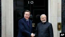 Perdana Menteri India Narendra Modi (kanan) disambut Perdana Menteri Inggris David Cameron di Downing Street No. 10 di London (12/11). (AP/Frank Augstein)