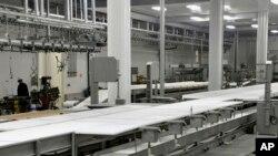 EB-5 programından elde edilen kaynakla açılan bir fabrikada birkaç işçi çalışırken görülüyor