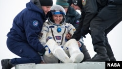 FILE - Expedition 38 Flight Engineer Sergei Ryazanskiy of the Russian Federal Space Agency, Roscosmos, is helped out of a Soyuz Capsule near the town of Zhezkazgan, Kazakhstan, in a March 11, 2014, photo.