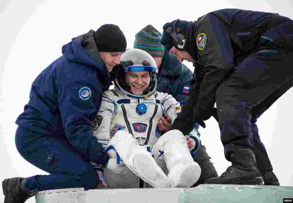 Expedition 38 Flight Engineer Mike Hopkins of NASA gives a thumbs up as he is helped from the Soyuz Capsule which landed in Kazakhstan.
