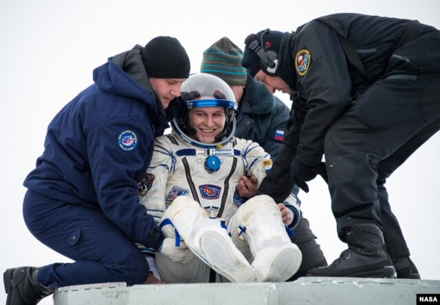 FILE - Expedition 38 Flight Engineer Sergey Ryazanskiy of the Russian Federal Space Agency, Roscosmos, is helped out of the Soyuz Capsule.