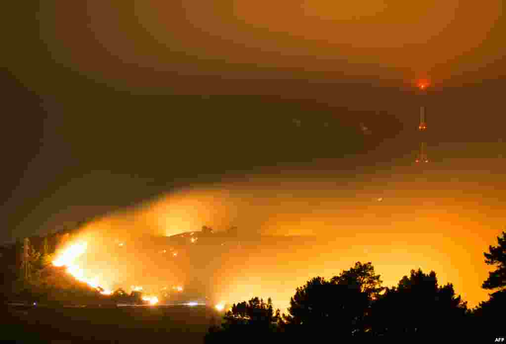 This handout picture provided by Oliver Watson of Ownz Productions shows flames from the wildfire on Worsleys Road in Christchurch, New Zealand, before sunrise.